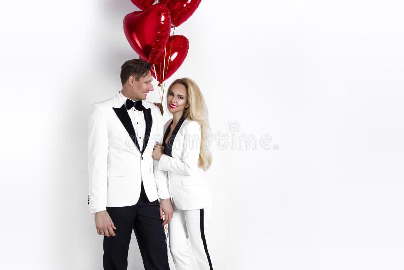 Ευτυχής όμορφη τοποθέτηση ζευγών στο άσπρο υπόβαθρο και κράτημα της καρδιάς μπαλονιών βαλεντίνος ημέρας s στοκ φωτογραφία με δικαίωμα ελεύθερης χρήσης