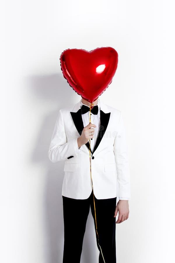 Ευτυχής όμορφη τοποθέτηση ζευγών στο άσπρο υπόβαθρο και κράτημα της καρδιάς μπαλονιών βαλεντίνος ημέρας s στοκ εικόνες