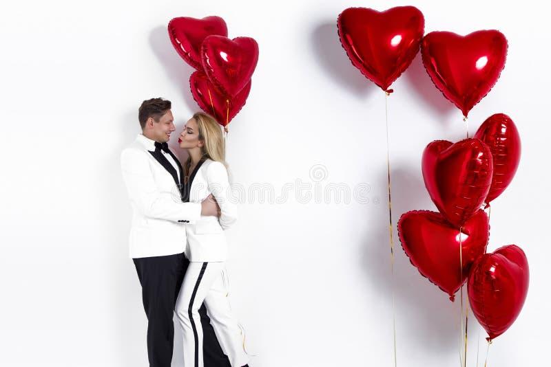 Ευτυχής όμορφη τοποθέτηση ζευγών στο άσπρο υπόβαθρο και κράτημα της καρδιάς μπαλονιών βαλεντίνος ημέρας s στοκ εικόνες με δικαίωμα ελεύθερης χρήσης