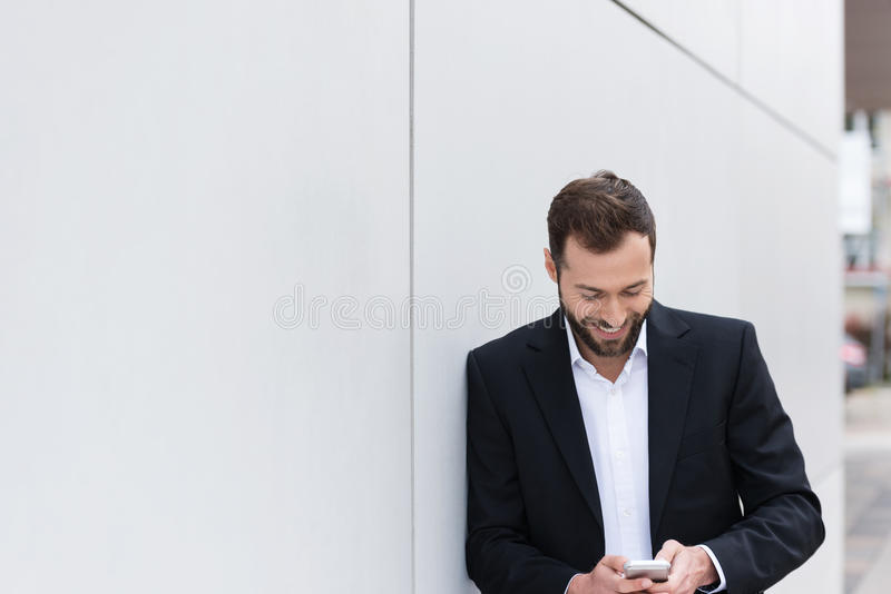 Ευτυχής όμορφος επιχειρηματίας Texting στο τηλέφωνο στοκ εικόνες