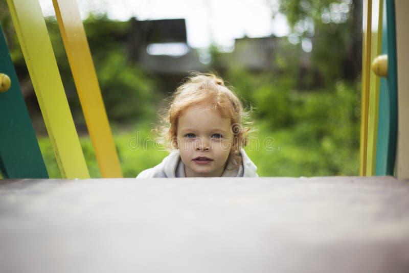 Ευτυχής όμορφος λίγο redhead κορίτσι αναρριχείται στη φωτογραφική διαφάνεια στην παιδική χαρά στοκ εικόνα με δικαίωμα ελεύθερης χρήσης