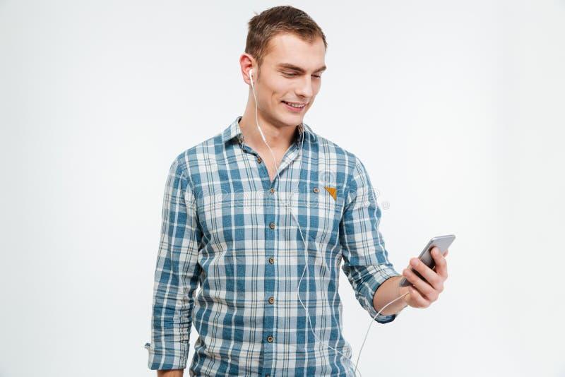 Ευτυχής όμορφος νεαρός άνδρας που ακούει τη μουσική από το κινητό τηλέφωνο στοκ εικόνες