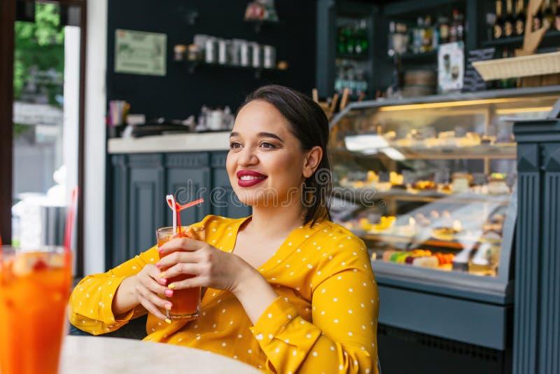 Ευτυχής όμορφος συν τη γυναίκα μεγέθους που χαμογελά και που πίνει τον υγιή καταφερτζή στον καφέ στοκ εικόνα