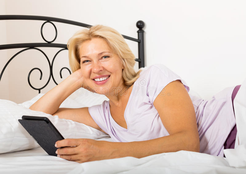 Ευτυχής ώριμη γυναίκα με το eBook στοκ εικόνα με δικαίωμα ελεύθερης χρήσης
