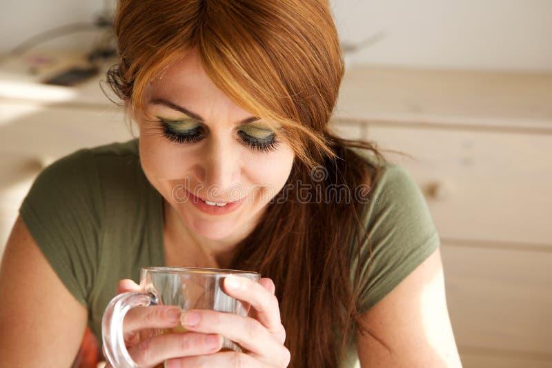 Ευτυχής ώριμη γυναίκα που έχει το πράσινο τσάι στοκ εικόνες