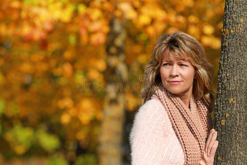 Ευτυχής ώριμη γυναίκα που κλίνει ενάντια σε ένα δέντρο μπροστά από το λιβάδι φθινοπώρου στοκ εικόνα