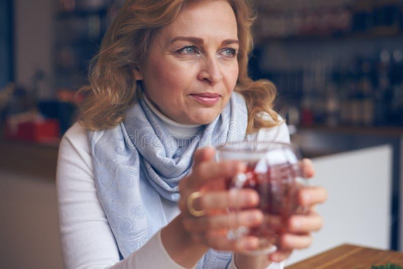Ευτυχής ώριμη γυναίκα που κρατά το καυτό φλυτζάνι του τσαγιού για να θερμάνει τα χέρια στοκ εικόνες
