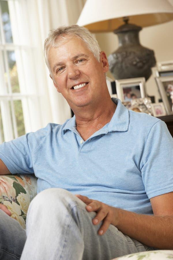 Ευτυχής ώριμη συνεδρίαση ατόμων στον καναπέ στο σπίτι στοκ φωτογραφία με δικαίωμα ελεύθερης χρήσης