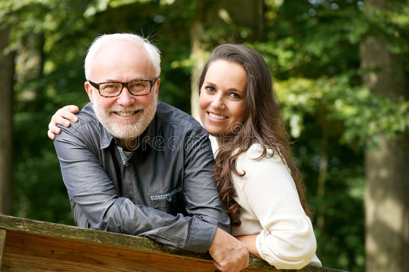 Ευτυχής ώριμος άνδρας που χαμογελά με τη νέα γυναίκα στοκ φωτογραφίες