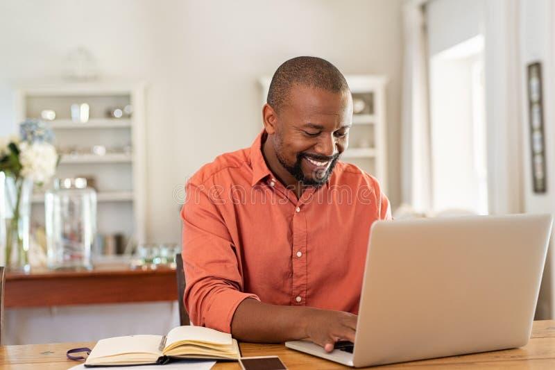 Ευτυχής ώριμος μαύρος που χρησιμοποιεί το lap-top στοκ εικόνες με δικαίωμα ελεύθερης χρήσης