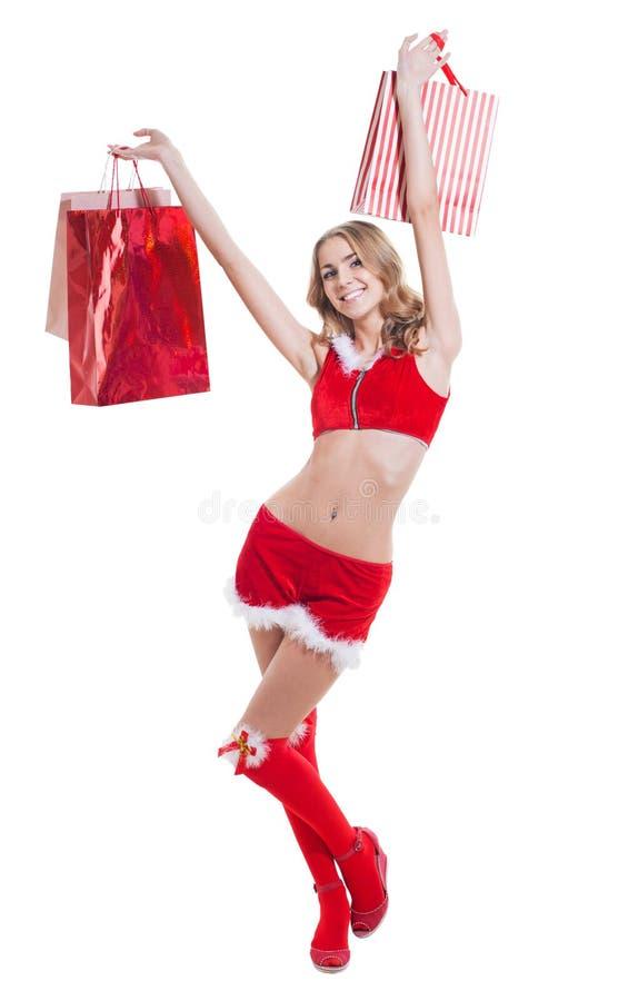 Ευτυχής beautyful γυναίκα στα κόκκινα ενδύματα Άγιου Βασίλη με τις τσάντες αγορών στοκ εικόνες με δικαίωμα ελεύθερης χρήσης
