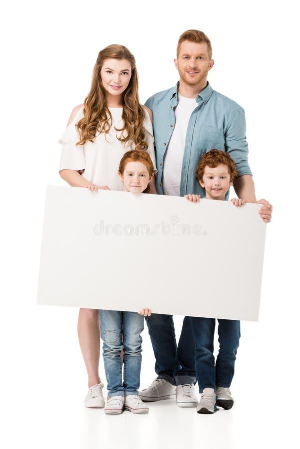 ευτυχής redhead οικογένεια με δύο παιδιά που κρατούν το κενό έμβλημα και που χαμογελούν στη κάμερα στοκ φωτογραφία