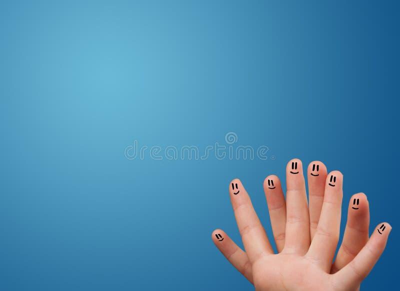 Ευτυχή δάχτυλα προσώπου smiley που εξετάζουν το κενό μπλε αντίγραφο υποβάθρου στοκ εικόνα με δικαίωμα ελεύθερης χρήσης