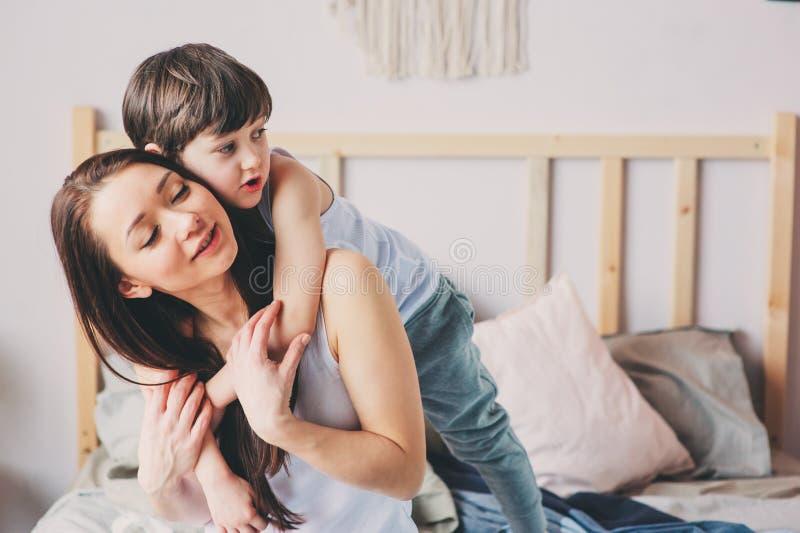 Ευτυχή αγκαλιάσματα μητέρων αγάπης με το γιο παιδιών το πρωί στο κρεβάτι στοκ εικόνες