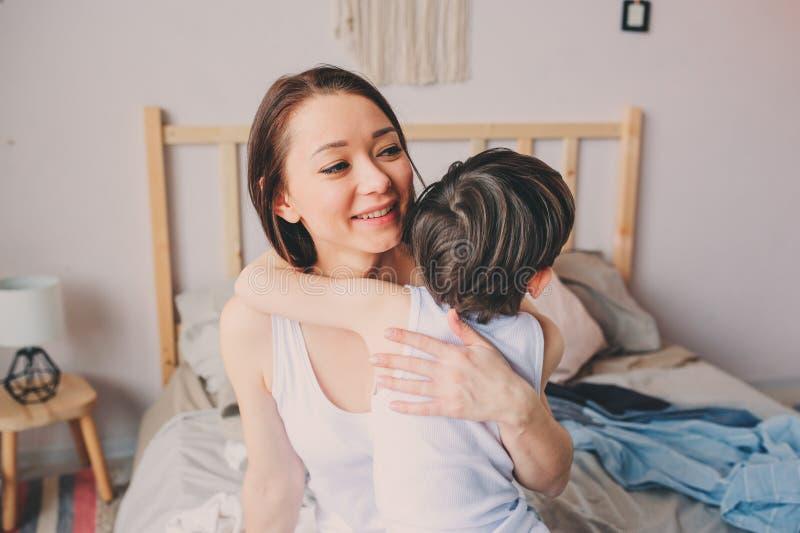 Ευτυχή αγκαλιάσματα μητέρων αγάπης με το γιο παιδιών το πρωί στο κρεβάτι στοκ εικόνα με δικαίωμα ελεύθερης χρήσης