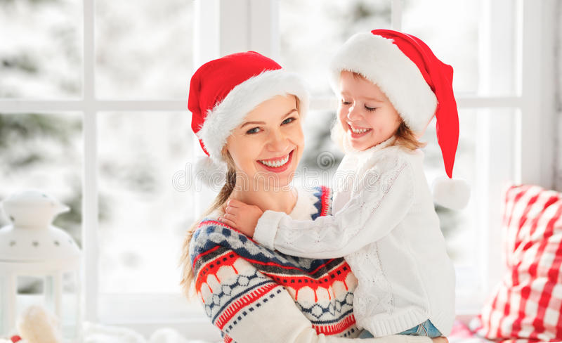 Ευτυχή αγκαλιάσματα κοριτσιών οικογενειακών μητέρων και παιδιών στο παράθυρο στο χειμώνα στοκ φωτογραφία