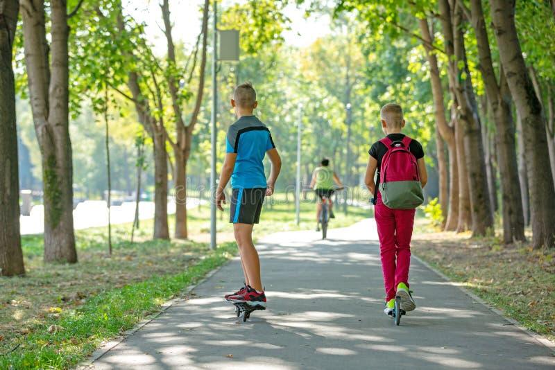 Ευτυχή αγόρια με τα σαλάχια και το μηχανικό δίκυκλο κυλίνδρων, που περπατούν στο δρόμο στο πάρκο, καλοκαίρι στοκ φωτογραφίες