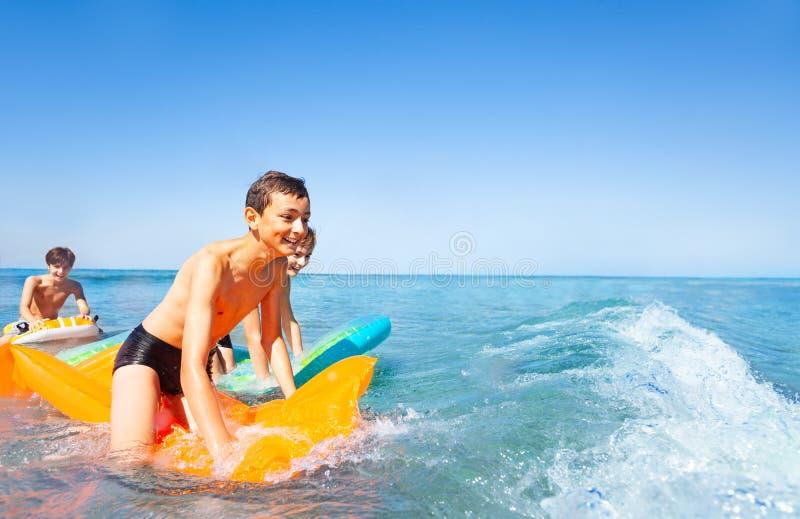 Ευτυχή αγόρια που οδηγούν τα κύματα στα στρώματα αέρα στοκ φωτογραφία με δικαίωμα ελεύθερης χρήσης