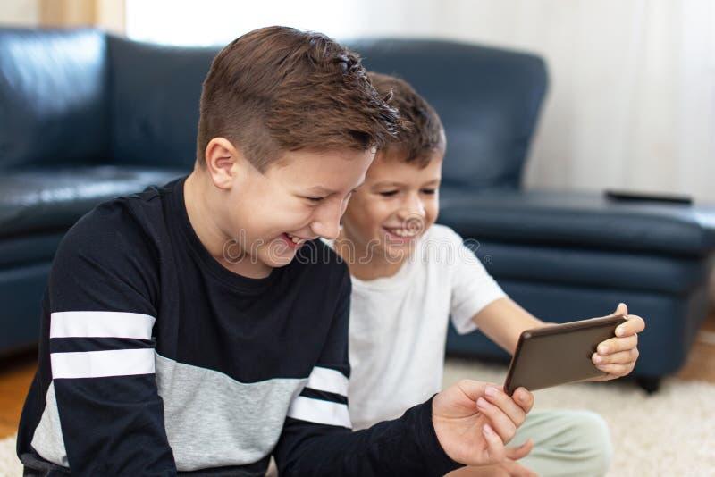Ευτυχή αγόρια χρησιμοποιώντας το smartphone στο σπίτι και γελώντας στοκ εικόνα