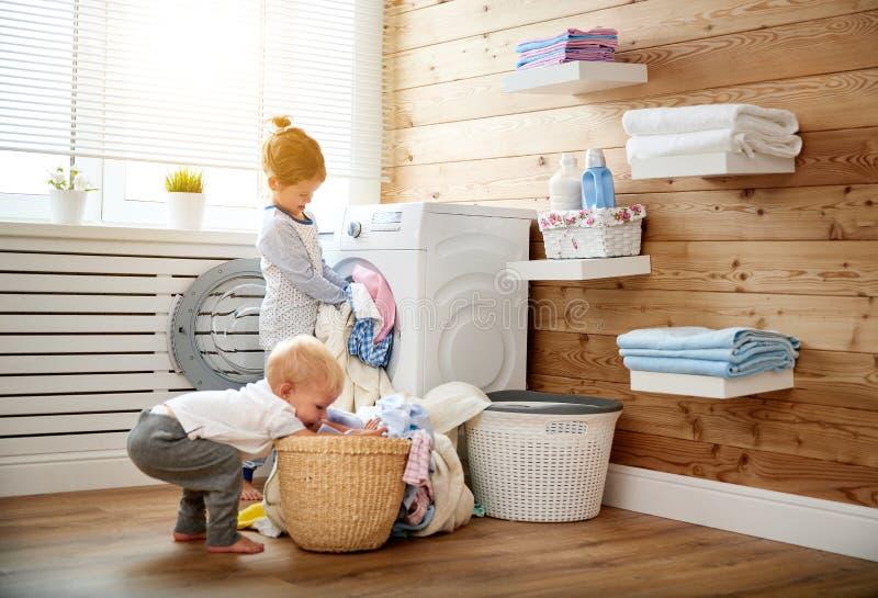 Ευτυχή αγόρι και κορίτσι παιδιών στο πλυντήριο φορτίων πλυντηρίων στοκ εικόνες