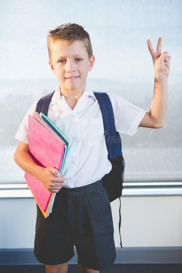 Ευτυχή βιβλία εκμετάλλευσης schoolkid και στάση στην τάξη στοκ φωτογραφία