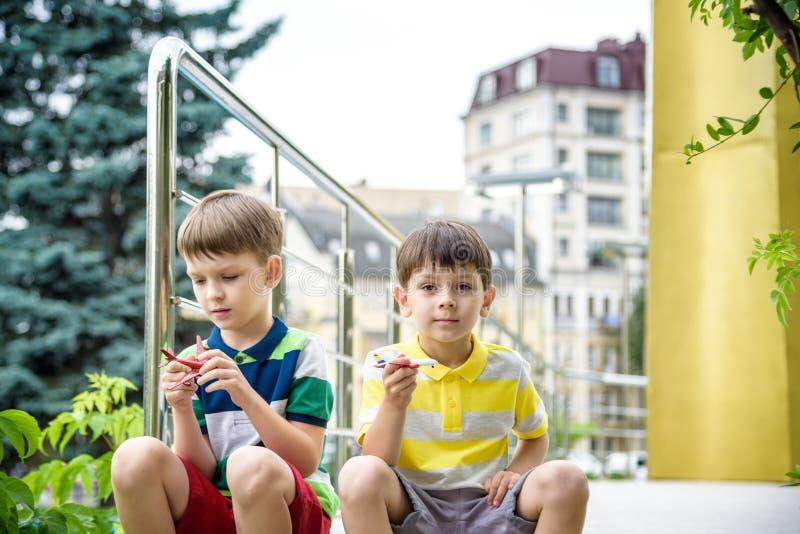 Ευτυχή δύο παιδιά αδελφών που παίζουν με το αεροπλάνο παιχνιδιών τη θερμή θερινή ημέρα Τα αγόρια εξετάζουν το αντίγραφο κλίμακας  στοκ φωτογραφία με δικαίωμα ελεύθερης χρήσης