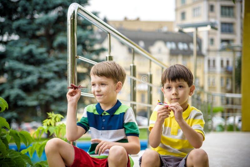 Ευτυχή δύο παιδιά αδελφών που παίζουν με το αεροπλάνο παιχνιδιών τη θερμή θερινή ημέρα Τα αγόρια εξετάζουν το αντίγραφο κλίμακας  στοκ εικόνες με δικαίωμα ελεύθερης χρήσης