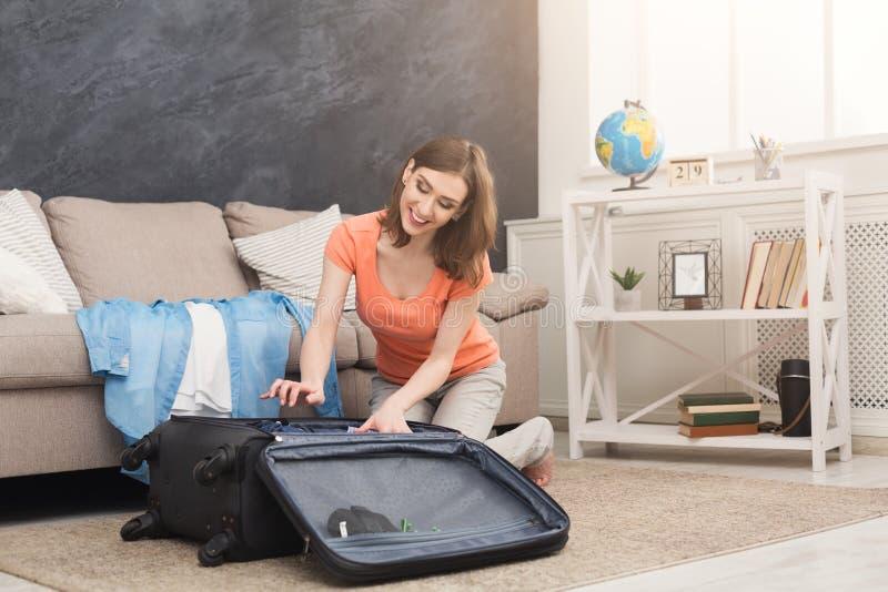 Ευτυχή ενδύματα συσκευασίας γυναικών στην τσάντα ταξιδιού στοκ φωτογραφία με δικαίωμα ελεύθερης χρήσης