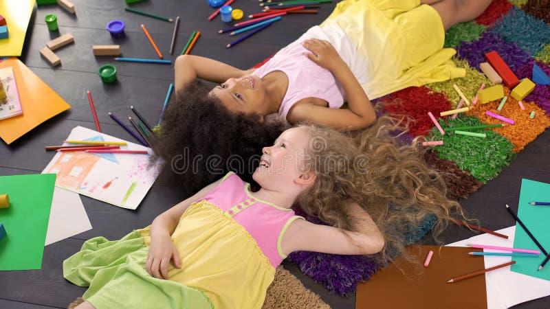 Ευτυχή θηλυκά αφροαμερικανός και ευρωπαϊκά παιδιά που χαμογελούν στο ζωηρόχρωμο τάπητα στοκ φωτογραφία