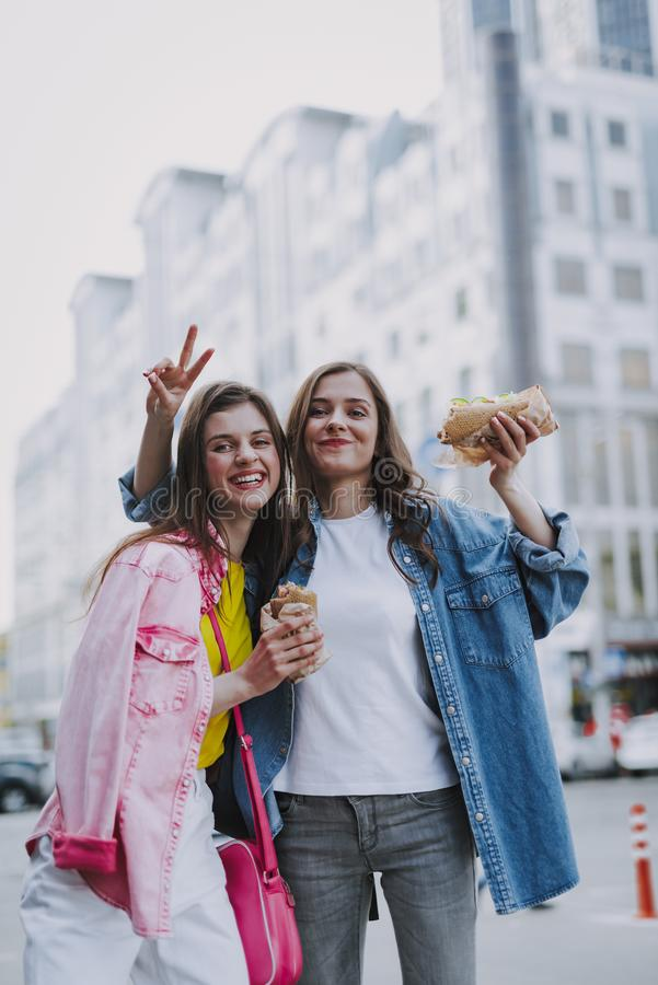 Ευτυχή θηλυκά που κάνουν την αστεία φωτογραφία με τα χοτ-ντογκ στοκ φωτογραφία