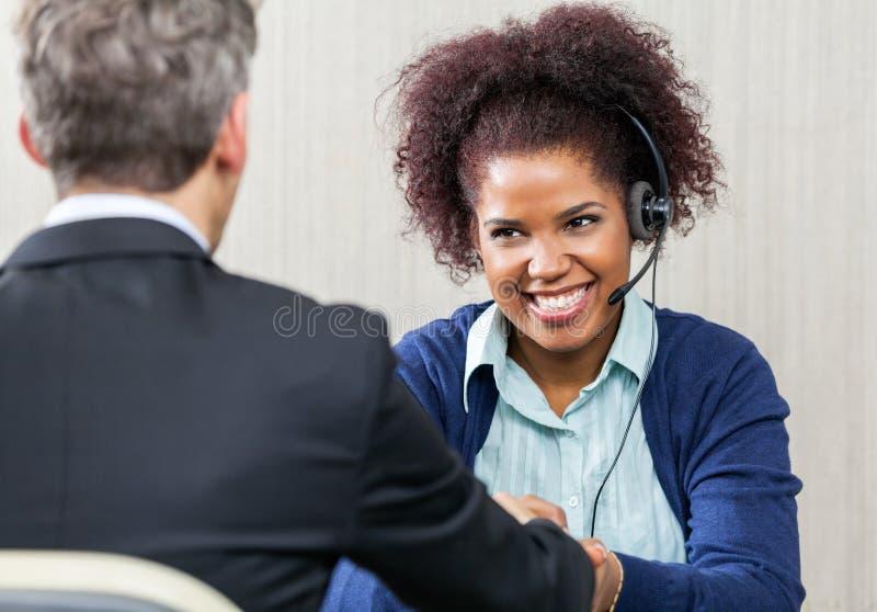 Ευτυχή θηλυκά χέρια τινάγματος πρακτόρων εξυπηρέτησης πελατών στοκ φωτογραφίες