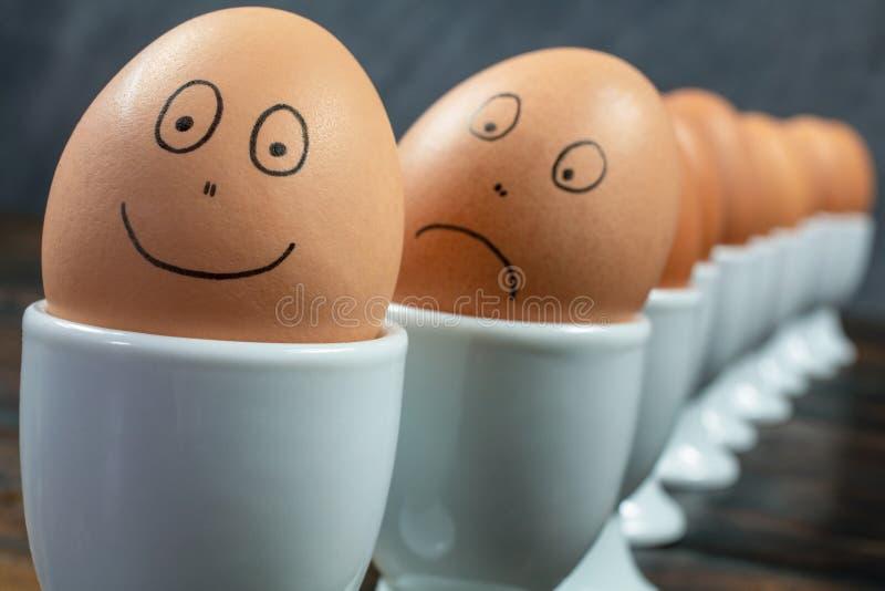 Ευτυχή και λυπημένα αυγά έννοιας συγκίνησης στα φλυτζάνια αυγών σε έναν πίνακα στοκ εικόνα με δικαίωμα ελεύθερης χρήσης