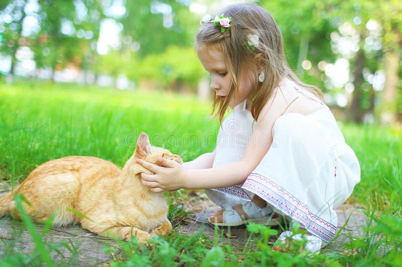 Ευτυχή κατοικίδια ζώα μικρών κοριτσιών η γάτα το καλοκαίρι υπαίθρια στοκ εικόνες