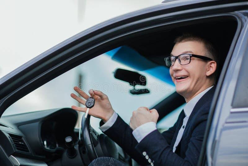 Ευτυχή κλειδιά εκμετάλλευσης επιχειρηματιών για το νέο αυτοκίνητό του στοκ φωτογραφίες