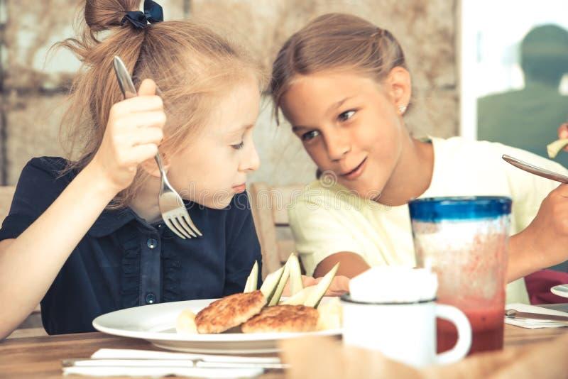 Ευτυχή κορίτσια αδελφών παιδιών που έχουν έναν χρόνο ανάπαυλας στο εστιατόριο καφέδων που μιλά μαζί τον τρόπο ζωής παιδικής ηλικί στοκ φωτογραφία