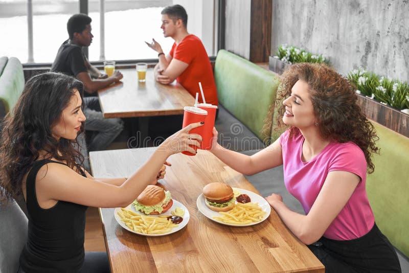 Ευτυχή κορίτσια που κάθονται στον καφέ γρήγορου φαγητού, clinking φλυτζάνια εγγράφου στοκ φωτογραφία με δικαίωμα ελεύθερης χρήσης