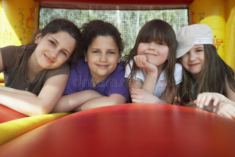 Ευτυχή κορίτσια που χαλαρώνουν σε Bouncy Castle στοκ εικόνα