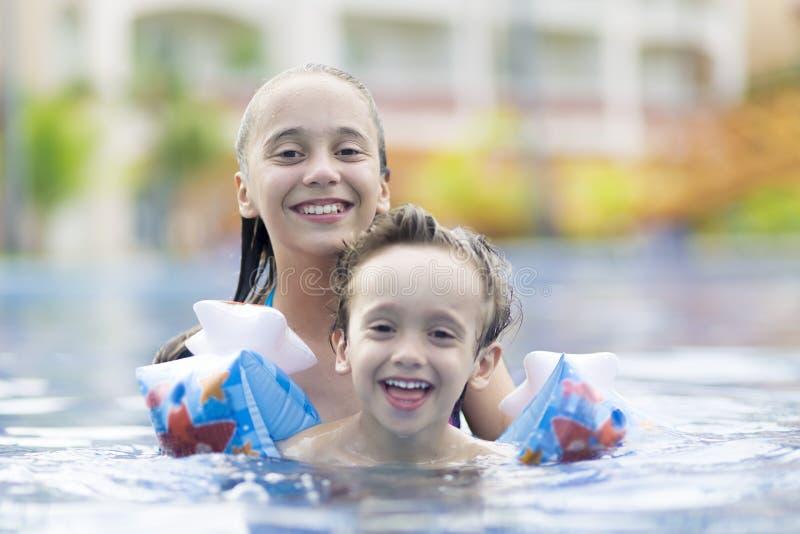 Ευτυχή κορίτσι και αγόρι που απολαμβάνουν στην πισίνα στοκ φωτογραφία με δικαίωμα ελεύθερης χρήσης