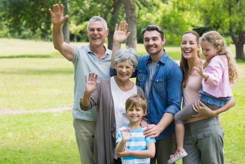 Ευτυχή κυματίζοντας χέρια πολυμελών οικογενειών στο πάρκο στοκ εικόνες
