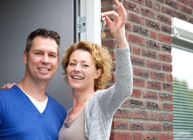 Ευτυχή κλειδιά εκμετάλλευσης ζευγών για το νέο σπίτι τους στοκ φωτογραφία