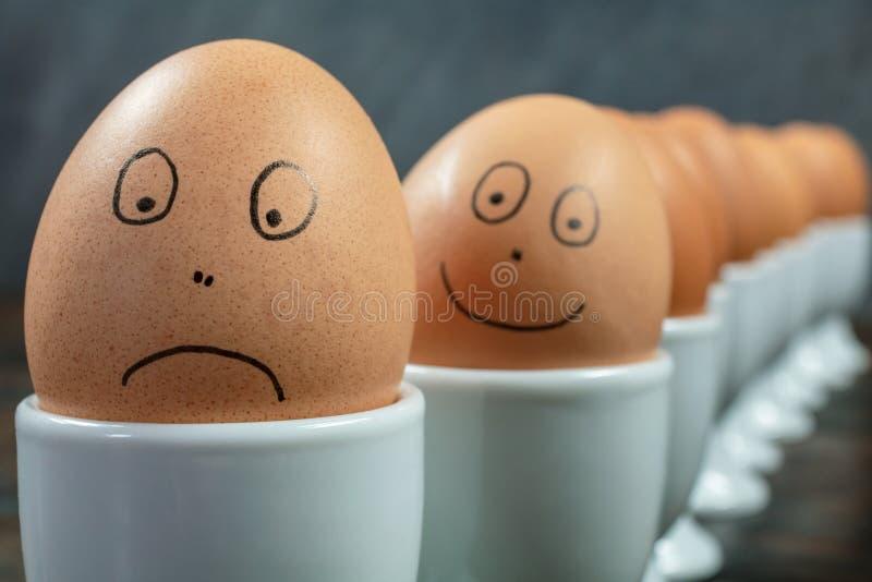 Ευτυχή λυπημένα συναισθηματικά αυγά έννοιας στα φλυτζάνια αυγών στοκ εικόνες