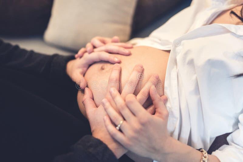 Ευτυχή μελλοντικά χέρια εκμετάλλευσης πατέρων και σχετικά με την κοιλιά της συζύγου στοκ εικόνες με δικαίωμα ελεύθερης χρήσης
