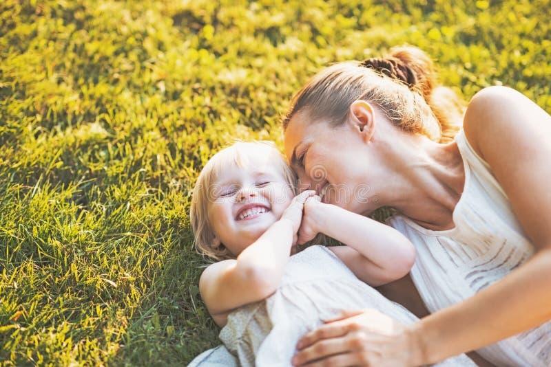 Ευτυχή μητέρα και μωρό που βάζουν στο λιβάδι στοκ φωτογραφία με δικαίωμα ελεύθερης χρήσης