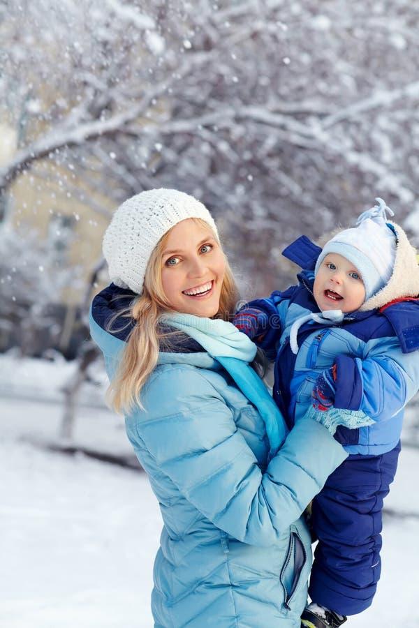 Ευτυχή μητέρα και μωρό στο χειμερινό πάρκο οικογένεια υπαίθρια στοκ εικόνες