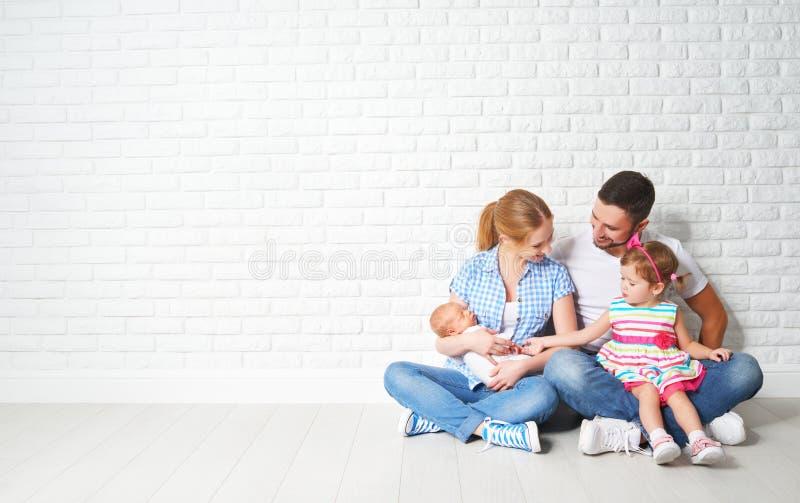 Ευτυχή μητέρα και παιδιά οικογενειακών πατέρων στον κενό τοίχο στοκ εικόνες