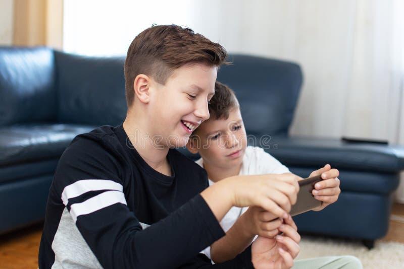 Ευτυχή μικρά παιδιά που χρησιμοποιούν το smartphone στο σπίτι στοκ εικόνες