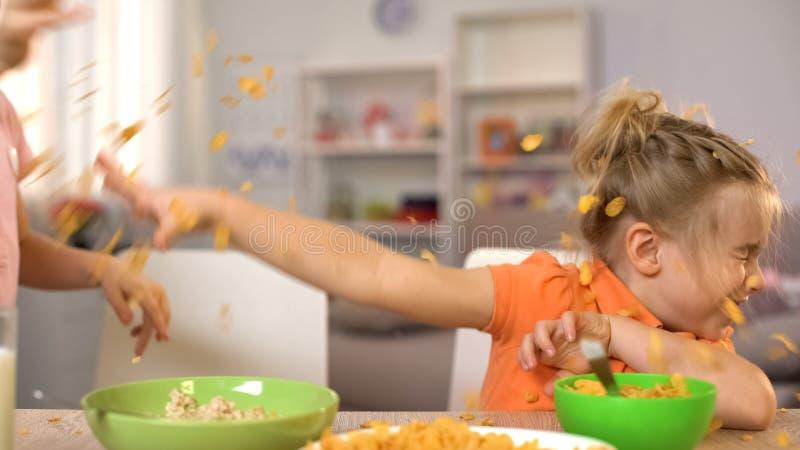 Ευτυχή μικρό παιδί και κορίτσι που ρίχνουν τα δημητριακά το ένα στο άλλο, που έχει τη διασκέδαση στο σπίτι στοκ φωτογραφίες