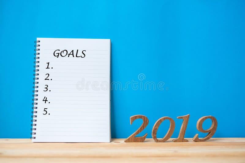 """2019 ευτυχή νέα έτη με το κείμενο στόχων σημειωματάριων """" """" και ξύλινος αριθμός στο διάστημα πινάκων και αντιγράφων στοκ εικόνα"""