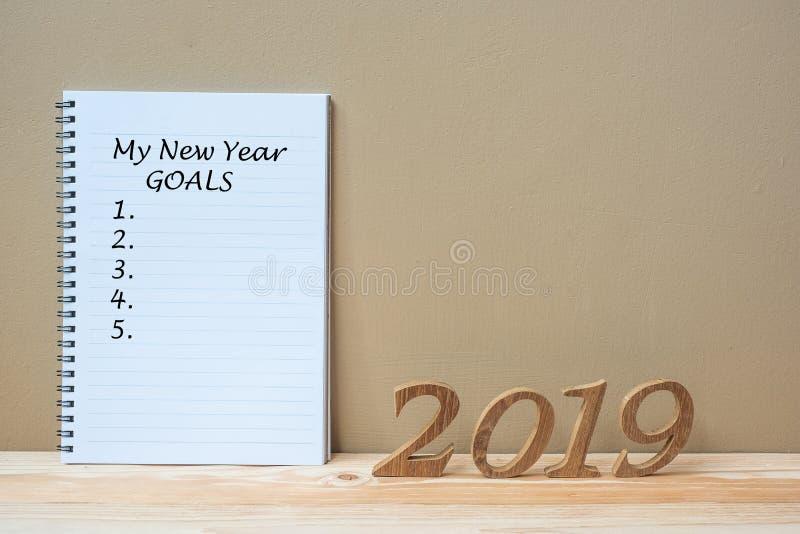 """2019 ευτυχή νέα έτη με το σημειωματάριο """" το νέο κείμενο στόχων έτους """" και ο ξύλινος αριθμός μου στο διάστημα πινάκων και αν στοκ εικόνα με δικαίωμα ελεύθερης χρήσης"""