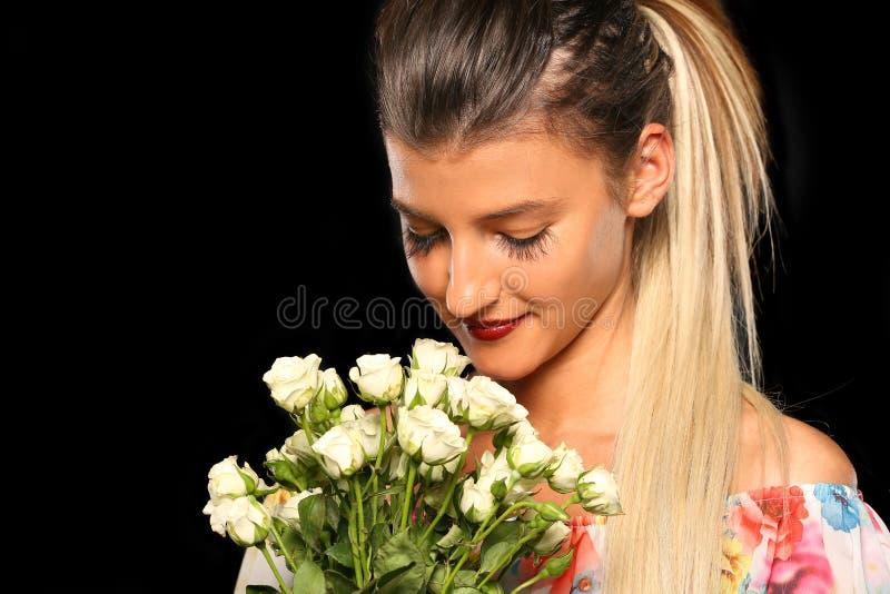 Ευτυχή νέα μυρίζοντας λουλούδια γυναικών στοκ εικόνα